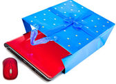 Red laptop and a computer mouse are packed into a gift packet by New yea — Stock Photo