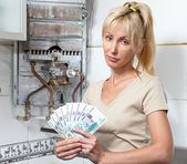 Housewife counts up money for repair of a gas water heater — Stock Photo