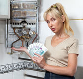 The sad woman the housewife counts up money for repair of a gas water heater — Stock Photo