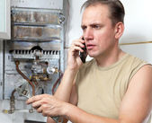 The man calls by phone to cause the repairman of gas water heater — Zdjęcie stockowe