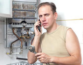 The man calls by phone to cause the repairman of gas water heater — Stock Photo