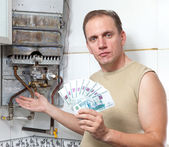 Man counts money for repair of a gas water heater — Stock Photo