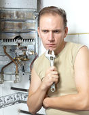 The man with a wrench thinks of repair of a gas water heate — Stock Photo