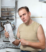 The man with a wrench looks the instruction on repair a gas water heater — Stock Photo