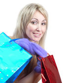 The young woman in bright mittens with elegant packages rejoices to winter sale — Stock Photo