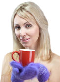 Portrait of the young blonde woman in fluffy mittens with a mug — Stock Photo