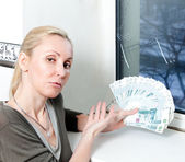 The sad young woman counts money for window repair with the burst, broken glass — Stock Photo