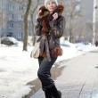 Stock Photo: Young womin jacket with fur collar on street in winter