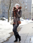 The young woman in a jacket with a fur collar on the street in the winter — Stock Photo