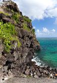 Black stones in the sea. Mauritius — Stock Photo