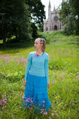 The beautiful young woman in a blue dress in the field at an ancient castle — Stock Photo