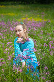 The happy young woman in the field of wild flowers — Stock Photo