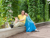 Young happy couple sits in the arbour twined greens — Stock Photo