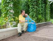 Pareja joven se sienta en los verdes arbour torcido — Foto de Stock