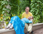 Young happy couple sits in the arbour twined greens — Foto de Stock