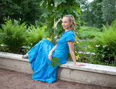 The young beautiful woman in a blue dress in the arbor twined a green bindwee — Stock Photo