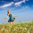 the happy young woman jumps in the field of camomiles — Stock Photo