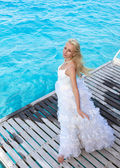 The young beautiful woman in a dress of the bride runs on waves of the see — Stock Photo