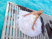 The young beautiful woman in a dress of the bride runs on waves of the see — Stockfoto