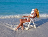 Young pretty woman in a beach chair at ocean — Stock Photo