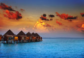 Houses on piles on water at the time sunset — Stock Photo