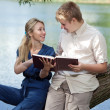 Young guy and the girl with textbooks on the bank of lake — Stock Photo