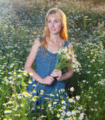 The beautiful young woman in the field with a bouquet of camomiles — Stock Photo