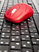 The red computer mouse on the black keyboard — Stock Photo