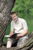 The young man with the book in park on the bank of lake — Stock Photo