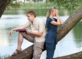 Young guy and the girl prepare for lessons, examination in spring park near lake — Stock Photo