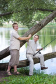 The father with the son on fishing. Rejoice to a biting — Stock Photo
