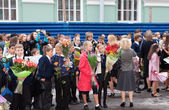 Children with flowers near the School on the first day of school on September 1, 2011 in Saint-Petersburg, Russia — Stock Photo