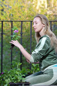 The young woman on a balcony lands petunia seedling — Stock Photo