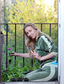 The young woman on a balcony lands petunia seedling — Zdjęcie stockowe