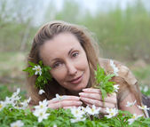 The young beautiful woman on a glade of blossoming snowdrops in the early sprin — Stock Photo