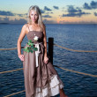 The young beautiful woman on a wooden platform over the sea — Stock Photo