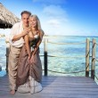 Loving couple on a wooden platform over the sea on the tropical island — Stock Photo #48062109