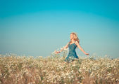 The happy young woman jumps in the field of camomiles,with a retro effect — Stock Photo