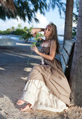The young beautiful woman in a romantic dress on a bench on a beach, tropics — Stock Photo
