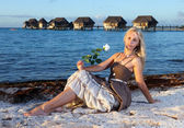 The young beautiful woman with a rose sits on sand at the sea edge — Stock Photo