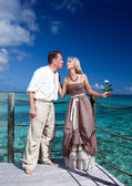 Loving couple on a wooden platform over the sea on the tropical island — Stock Photo