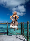 The beautiful woman jumps up on a wooden platform over the sea — Stock Photo