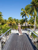 The beautiful woman in a long dress on the wooden bridge near the sea. — Stock Photo