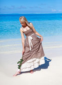 The young beautiful woman in a romantic dress with a rose on sand at the sea edge — Stock Photo