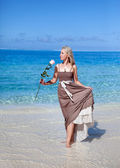 The young beautiful woman in a romantic dress with a rose on sand at the sea edg — Stock Photo