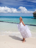 The young beautiful woman in a bride dress standing at sea edg — Stock Photo