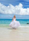 De jonge mooie vrouw in een jurk van de bruid draait op de golven van de zee — Stockfoto