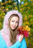 The beautiful woman in autumn park with an armful of maple leaves — Stock Photo