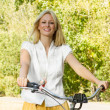 Happy young woman on the bicycle — Stock Photo #13311876