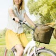 Happy young woman on the bicycle — Stock Photo #13313471